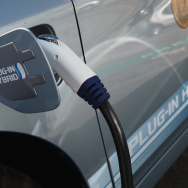 A power cable from a vehicle charging station is seen plugged into the side of a Toyota Prius plug-in hybrid August 25, 2010 in San Francisco, California.