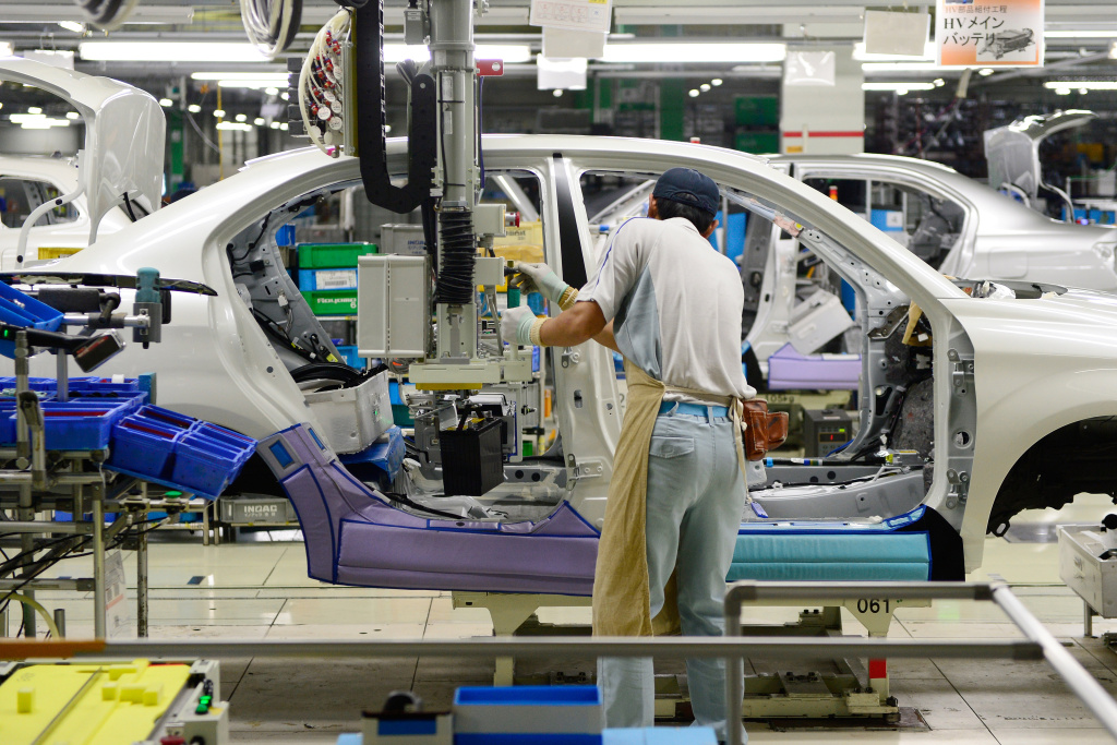 A Toyota Motor employee fixes the main battery of the hybrid system on an assembly line for the Corolla Axio at a plant of the company's subsidiary Toyota Motor East Japan in the village of Ohira, Miyagi prefecture, northern Japan, on August 23, 2013.