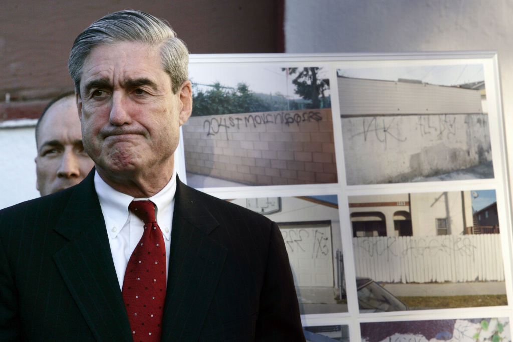FBI Director Robert Mueller during a news conference announcing anti-gang measures after the murder of Cheryl Green, Thursday Jan. 18, 2007 in Wilmington, Calif. Authorities announced an offensive against the Hispanic gang allegedly behind the racially charged shooting, the first part of what they said will be a major crackdown on street gangs this year. In the background photos of the 204th Street gang graffiti.