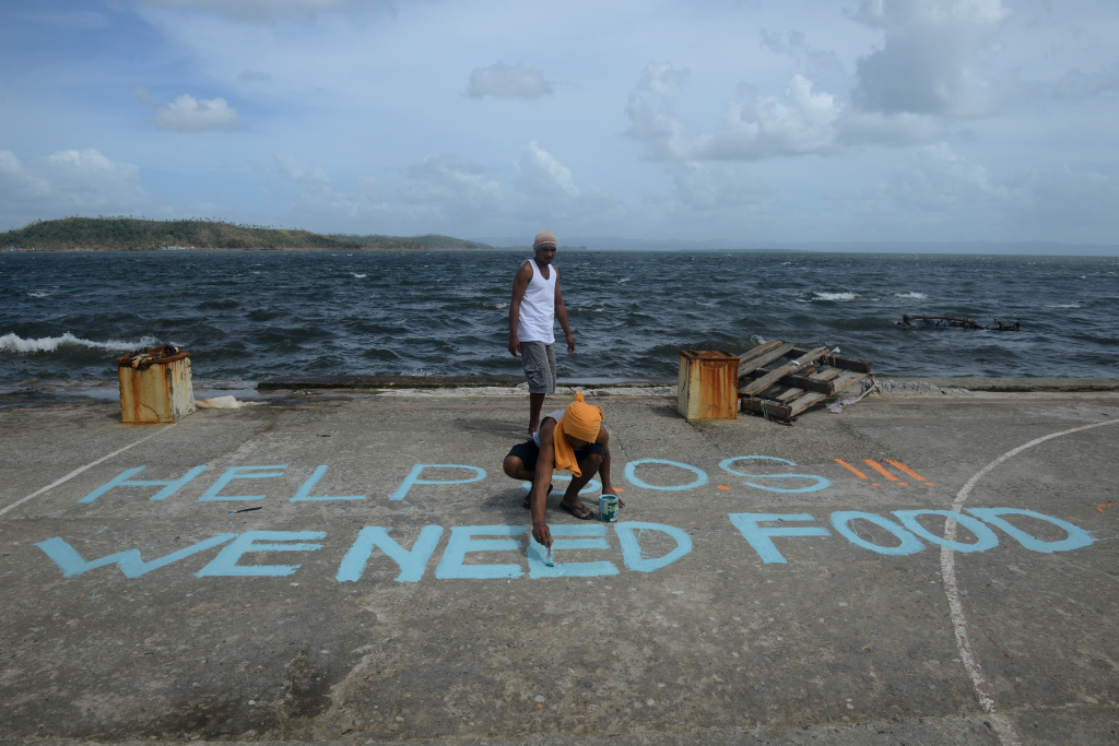 A man paints a message on a baskeball court that reads 'Help SOS We Need Food' at Anibong in Tacloban, eastern island of Leyte on November 11, 2013. Hundreds of Philippine soldiers and police poured into a city devastated by Super Typhoon Haiyan on November 11 to try to contain looting that threatens an emergency relief effort.