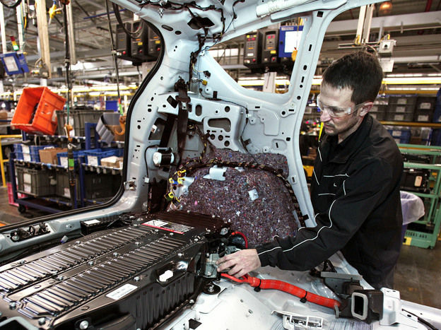 The Commerce Department said economic growth grew at a 3.1 percent rate in the third quarter of 2012. Here, a worker at a Ford plant in Michigan plugs a batter into a Ford C-MAX plug-in hybrid vehicle.