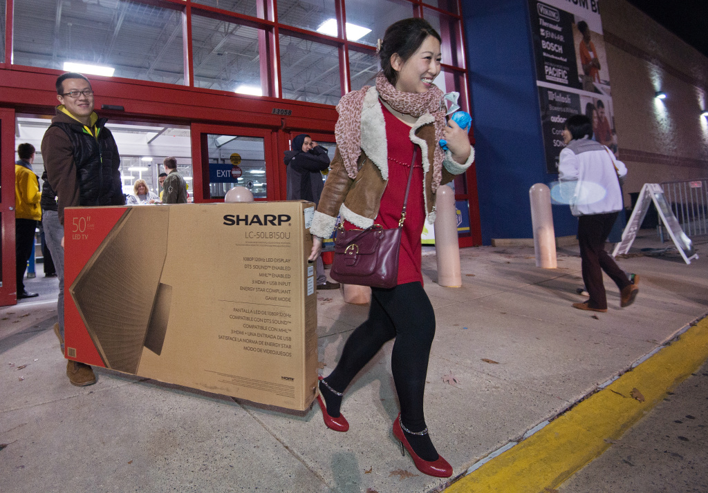Black Friday shoppers carry out a flat screen tv, seen here on Thursday November 28, 2013, at a Best Buy. More than a dozen US retailers opened their doors to shoppers one day ahead of the famed-Black Friday shopping day.