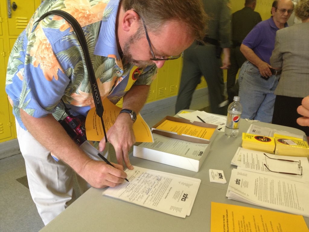 A man signs a petition drawn up by the Sherman Oaks Homeowners Association that outlines suggestions for how the FAA should regulate helicopters in Los Angeles.