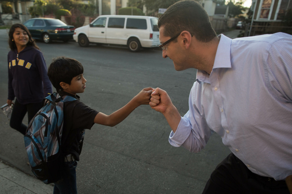 Mayoral candidate Emanuel Pleitez fist bumps with a Sabaq. Pleitez has focussed on canvassing poorer, Latino neighborhoods since his campaign started in July.
