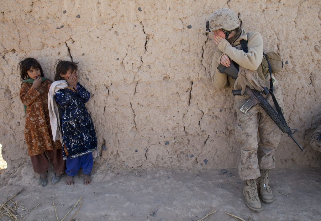 Corporal Catherine Broussard, 22, a US Marine with the FET (Female Engagement Team) 1st Battalion 8th Marines, Regimental Combat team II tries to communicate with some Afghan girls during a village medical outreach on November 23, 2010 in Boldoc, in Helmand province, Afghanistan.