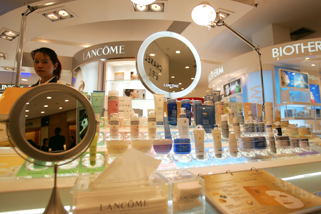 A Chinese Lancome Cosmetic Saleswoman waits for customers in the Friendship Shopping Mall which aims to attract the luxury customers in Guangzhou China November 25 2005.
