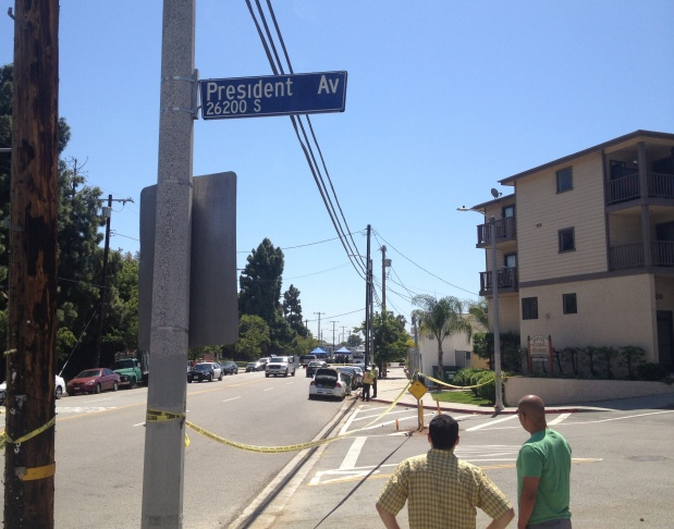 Two onlookers stare south on Anaheim Street in Harbor City Saturday, May 3, 2014 as LAPD investigators continue gathering evidence from the scene of a traffic collision that killed one officer.