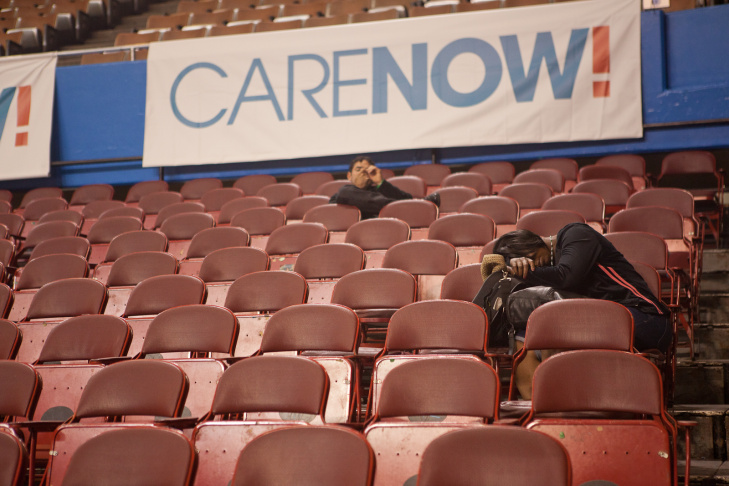 An optometrist performs an eye exam on a patient at CareNow's free clinic in the Los Angeles Sports Arena on Thursday.
