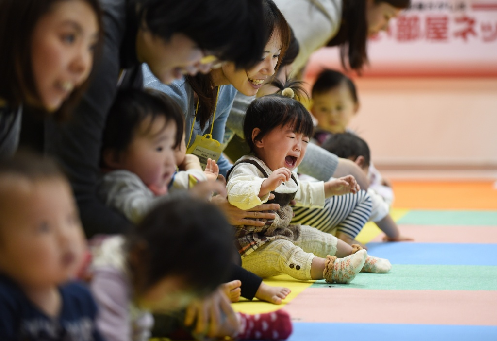 A mother tries to put her crying baby on the starting line during the Baby Super Crawl Dash at an event for young parents in Yokohama, in suburban Tokyo, on November 23, 2014. Ten babies took part in the four-metre (13-ft) race, with some 800 babies in total in the overall event, after being selected to join by the promoters.