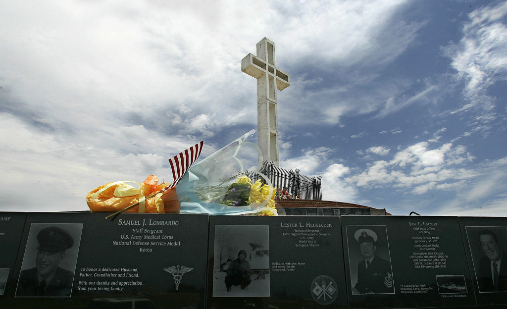 A flag and flowers adorn one of the walls of memorial plaques at the Mount Soledad National War Memorial Monday July 3, 2006, in San Diego.