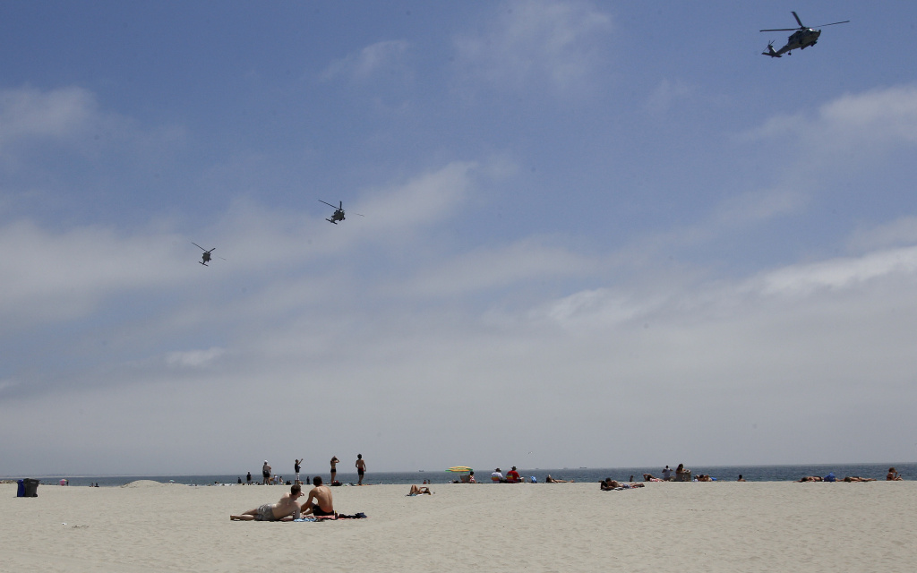 In this May 22, 2012 file photo, part of a Navy helicopter squadron flies over beach goers on the Coronado Beach in Coronado, Calif.