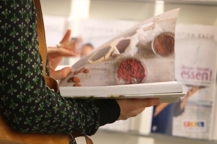 A woman reads a cookbook at the book fai