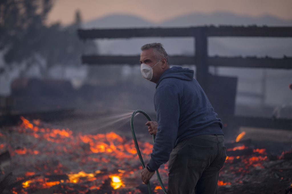 SUNLAND, CA - DECEMBER 05: A resident holds a leaking hose on his burning property during the Creek Fire on December 5, 2017 in Sunland, California. Strong Santa Ana winds are rapidly pushing multiple wildfires across the region, expanding across tens of thousands of acres and destroying hundreds of homes and structures.  (Photo by David McNew/Getty Images)