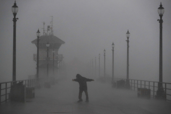 A man struggles against gusty wind and heavy rain as he walks along a pier Friday, Feb. 17, 2017, in Huntington Beach, Calif. A major Pacific storm has unleashed downpours and fierce gusts on Southern California, triggering flash flood warnings and other problems. (AP Photo/Jae C. Hong)