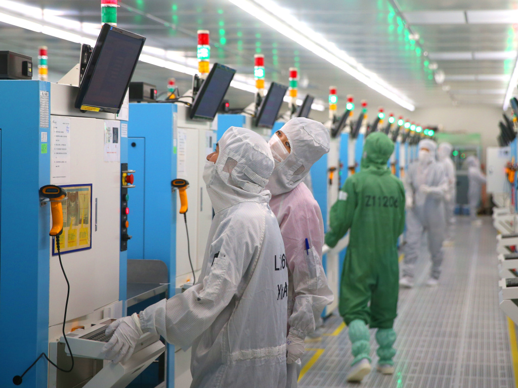 The Senate is expected to approve incentives for U.S. companies to compete with China on technology. Here, employees work this week at a Chinese factory producing silicon wafers.