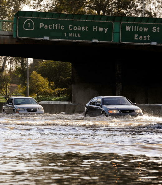 Cars make their way through the flooded north and southbound lanes of 710 Long Beach Freeway, the main artery to Long Beach and Los Angeles ports, on January 19, 2010 in Long Beach, California.