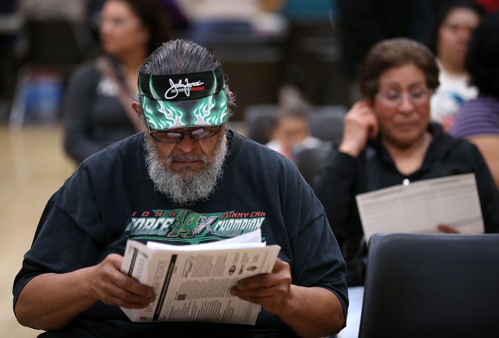 File photo: Frank Vigil looks over paperwork as he waits to register for health care insurance during an enrollment fair at Ambrose Community Center on March 28, 2014, in Bay Point, California.