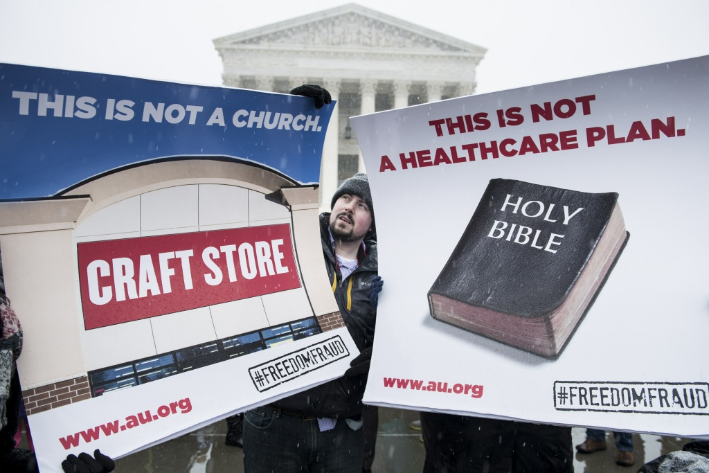 Activists hold signs outside the Supreme Court March 25, 2014 in Washington, DC. The Supreme Court heard arguments today in Sebelius v. Hobby Lobby Stores, Inc if for profit corporations can refuse to cover contraceptive services in their employee's healthcare for religious beliefs.