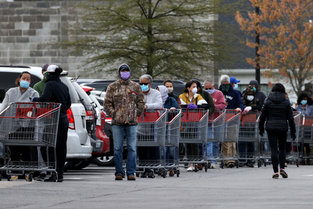 Customers wear face masks to prevent the spread of the novel coronavirus as they line up to enter a Costco Wholesale store April 16, 2020 in Wheaton, Maryland.