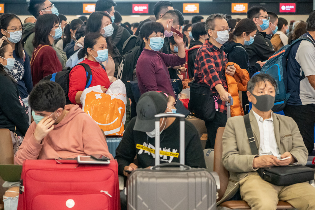 Travellers wearing face mask wait at the departure hall of West Kowloon Station in Hong Kong, China.