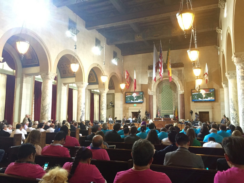 Supporters wear pink and blue Lyft and Uber shirts on the right, white taxi shirts on the left, at a Los Angeles City Council meeting on Tuesday, Aug. 18, 2015.