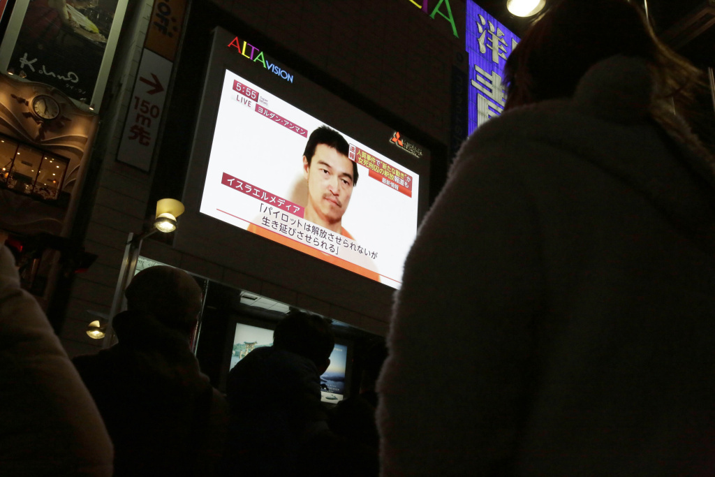 Passersby watch a TV news program Wednesday in Tokyo reporting on a video posted on YouTube by extremists that purports to show Japanese hostage Kenji Goto. Jordan says it is prepared to meet the demands of Islamic State militants in order to save the life of a Jordanian hostage.