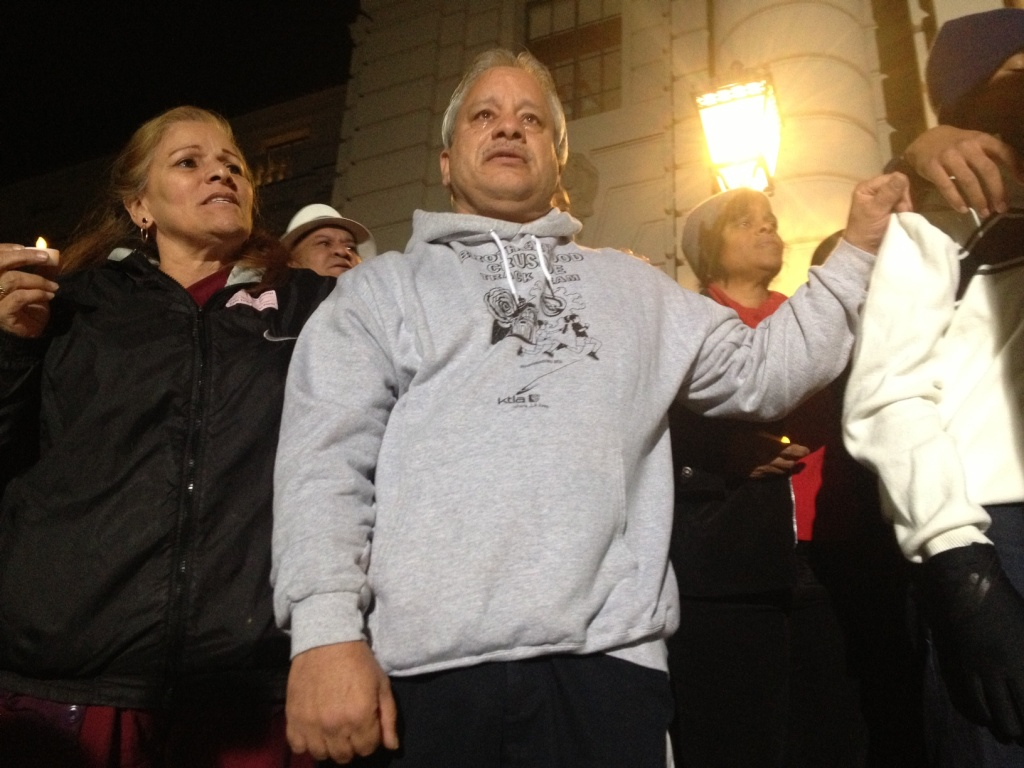 Friends of Victor McClinton hold on to each other to show support during a candlelight vigil held December 27 at Pasadena City Hall.