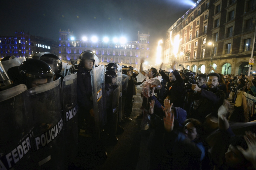 Members of Federal Police (L) confront protesters (R) outside Mexico's National Palace on Zocalo square in Mexico City, on November 20, 2014, over the safe return of 43 students who went missing in southern Mexico after an attack by gang-linked police last September 26. Protesters angry at the presumed massacre of 43 students clashed with police after a massive march demanding President Enrique Pena Nieto's resignation. AFP PHOTO/Alfredo ESTRELLA (Photo credit should read ALFREDO ESTRELLA/AFP/Getty Images)