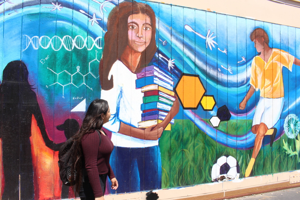 Dafne walks by a mural painted by students in her high school in San Jose, Calif on May 23, 2019.