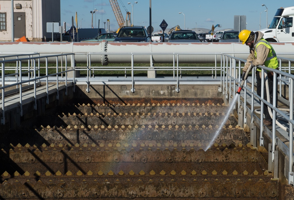 A worker cleans a wastewater pool at DC Water's Blue Plains plant in Washington, DC, on November 23, 2015. The U.S. EPA and the San Diego Regional Water Quality Control Board on Monday approved the city's permit application to operate the Point Loma Wastewater Treatment Plant for another five years despite it being the only facility of its kind not to meet federal standards.