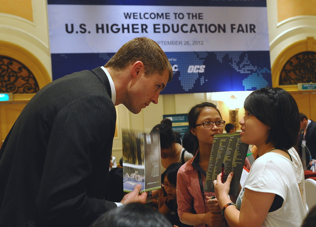 Chris Anderson (L), Assistant Director for International Admissions from US's Portland State University talks with a visiting Vietnamese student during a US Higher Education Fair in Hanoi on September 26, 2012.