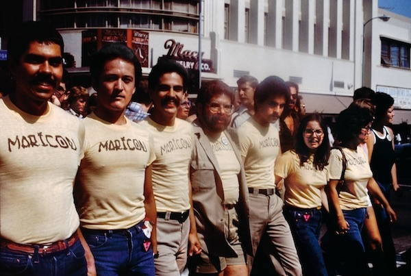 "Participants in the Christopher Street West Pride parade wearing Joey Terrill's ""malflora"" and ""maricón"" T-shirts, June 1976. This picture and one of the shirts is on display at the exhibit, ""Axis Mundo: Queer Networks in Chicano L.A."""