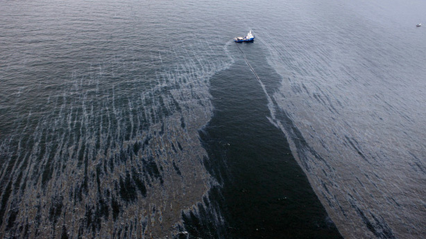 A boat with an oil boom tries to contain the spill, approximately seven miles from where the oil rig sunk last week.