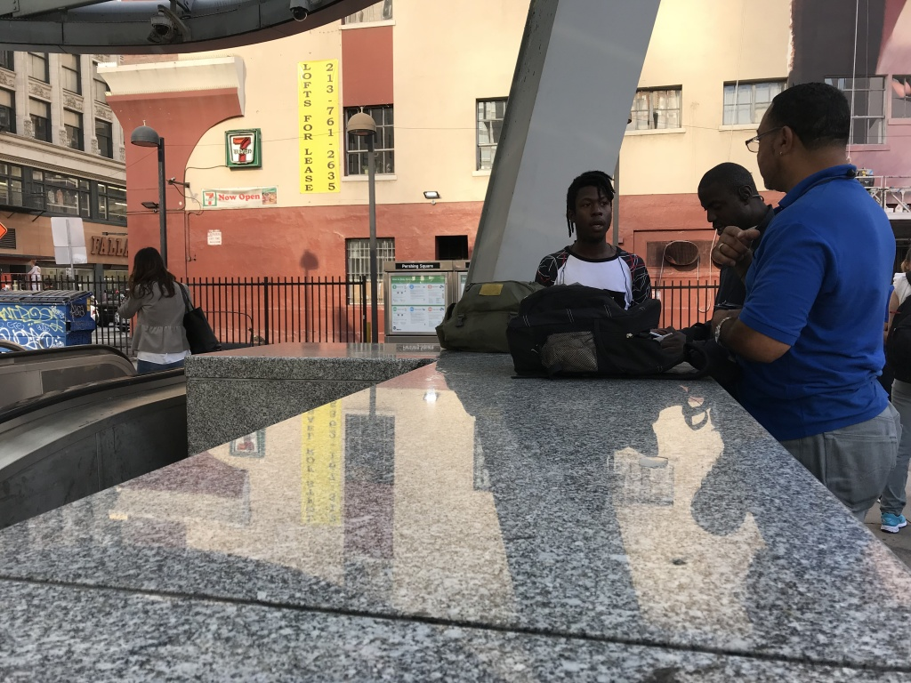 Julian Turner (right), part of Metro's homeless outreach team, chats with two young men outside the Pershing Square stop.