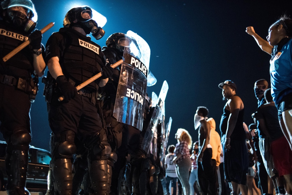 CHARLOTTE, NC - SEPTEMBER 21: Police officers face off with protesters on the I-85 (Interstate 85)during protests in the early hours of September 21, 2016 in Charlotte, North Carolina. The protests began last night, following the fatal shooting of 43-year-old Keith Lamont Scott by a police officer at an apartment complex near UNC Charlotte. (Photo by Sean Rayford/Getty Images)