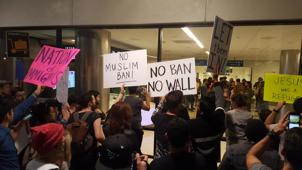 FILE: Protesters hold signs outside Terminal 2 at Los Angeles International Airport on Sunday, Jan. 29, 2017, amid calls to release immigrants detained under President Donald Trump's initial executive order banning travel from several majority-Muslim nations.
