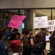 Protesters hold signs outside Terminal 2 at Los Angeles International Airport on Sunday, Jan. 29, 2017, amid calls to release immigrants detained under President Donald Trump's executive order effectively banning travel from seven majority Muslim nations.