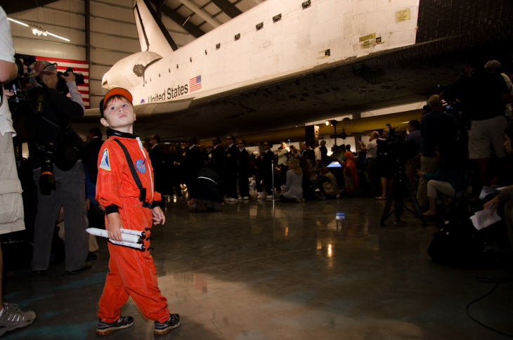 Sasha Tibelius, 4, holds a model rocket during the grand opening of the Space Shuttle Endeavour Exhibition at the California Science Center.