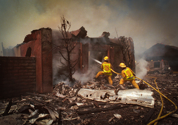Firefighters battle flames from a burning home in Cerritos, Calif., in this Aug. 31, 1986 file photo, as they straddle pieces of fuselage from an AeroMexico jetliner.
