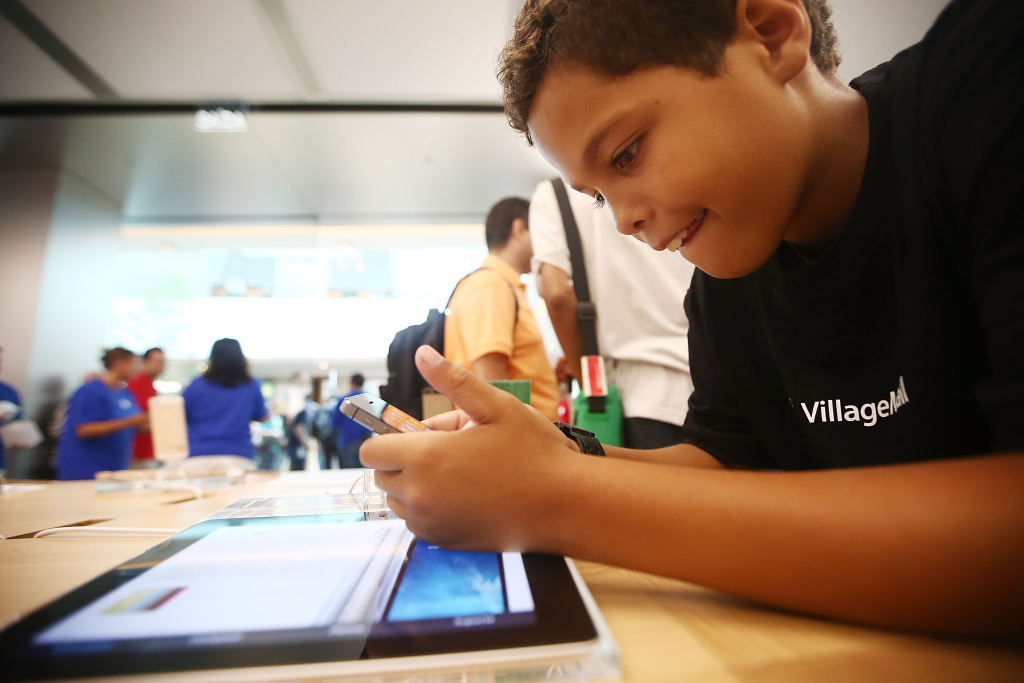 A boy plays with an iPhone in Brazil's first Apple retail store minutes after it opened to the public for the first time in the Village Mall shopping center on February 15, 2014 in Rio de Janeiro, Brazil.