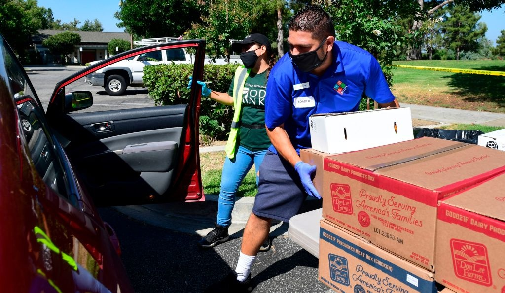 Volunteers help load boxes of food into vehicles at a food bank in the Los Angeles County city of Duarte, California on July 8, 2020 as the record for most coronavirus cases in a single day is set in California.