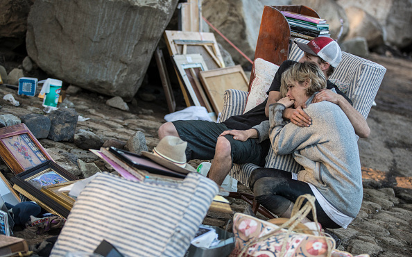 MONTECITO, CA - JANUARY 11: Travis Zehntner comforts Teresa Drenick, among belongings of her sister Rebecca Riskin was killed in the mudslide along San Ysidro Creek on January 11, 2018 in Montecito, California. 17 people have died and hundreds hundreds of homes have been destroyed or damaged after massive mudslides crashed through Montecito, California early Tuesday morning. (Photo by Brian van der Brug/Los Angeles Times via Getty Images)