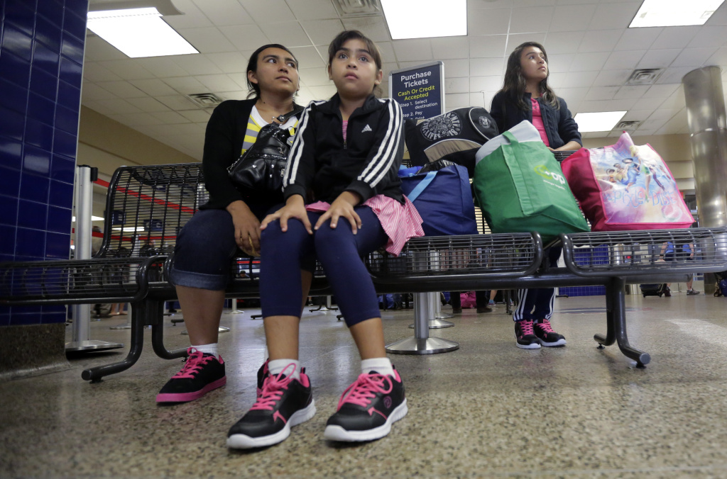 Immigrants from El Salvador and Guatemala who entered the country illegally wait at a bus station after they were released from a family detention center, Tuesday, July 7, 2015, in San Antonio. Women and children are being released from immigrant detention centers faster on bond, with many mothers assigned ankle monitoring bracelets in lieu of paying. (AP Photo/Eric Gay)