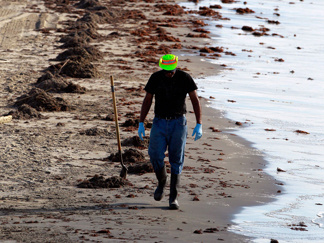 A worker cleans up oil from the Deepwater Horizon spill along the beach Sunday in Grand Isle, La.