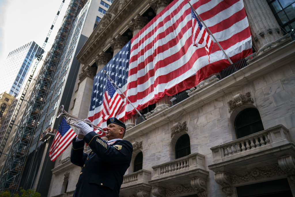 Mario Tronti, a member of the 42nd Infantry Division of the U.S. National Guard, performs 'Taps' as an American flag is raised on the facade of the New York Stock Exchange (NYSE), November 10, 2017 in New York City.