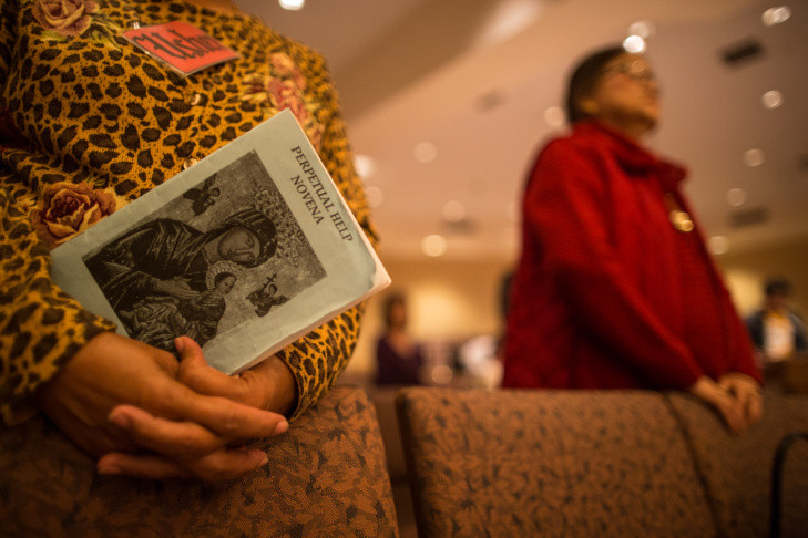 A woman reads from a miniature prayer book during a memorial and fundraising mass at St. Philomena Church in Carson, Calif.