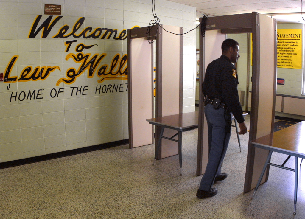 Police Officer Jeff Tatum passes through a metal detector at Lew Wallace High School.