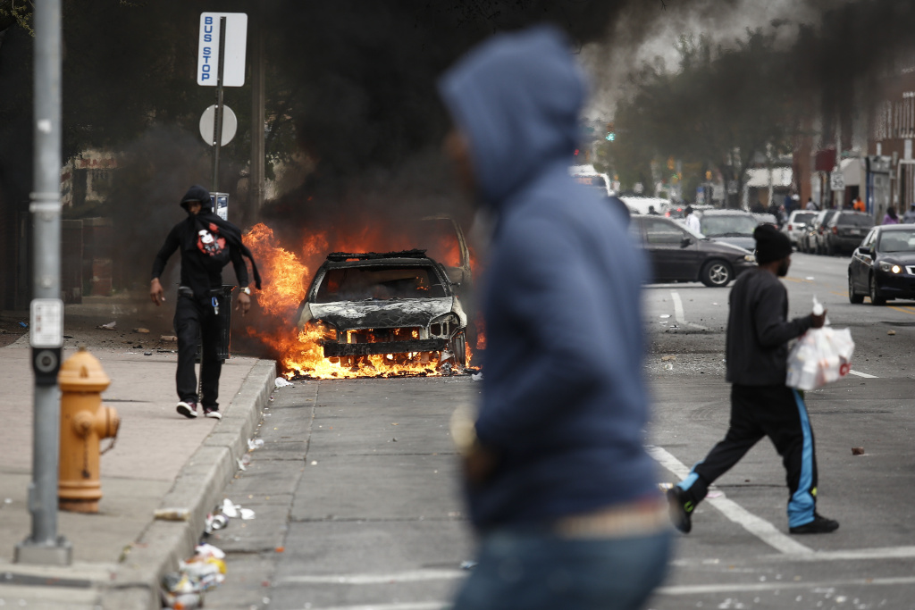BALTIMORE, MD - APRIL 27:  People walk past burning cars near the intersection of Pennsylvania Avenue and North Avenue, April 27, 2015 in Baltimore, Maryland. Riots have erupted in Baltimore following the funeral service for Freddie Gray, who died last week while in Baltimore Police custody. (Photo by Drew Angerer/Getty Images)