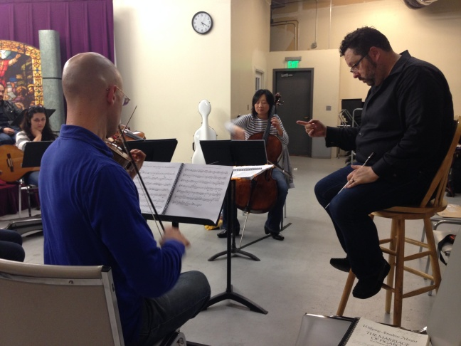 The cast of 14 for the first staged production of ¡Figaro! (90201) practices with the orchestra.