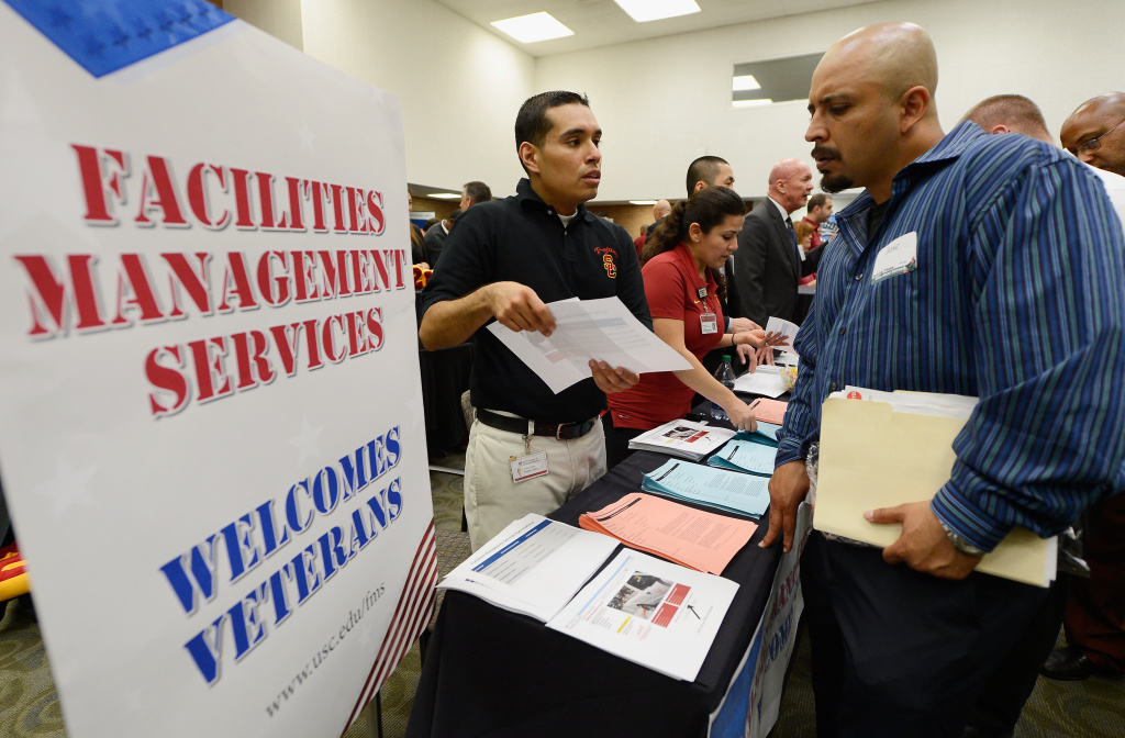 U.S. Marine Corps veteran Jose Navarrete (R) listens to Brian Mendez with University of Southern California facilities management services as he looks for employment during a jobs fair for veterans called